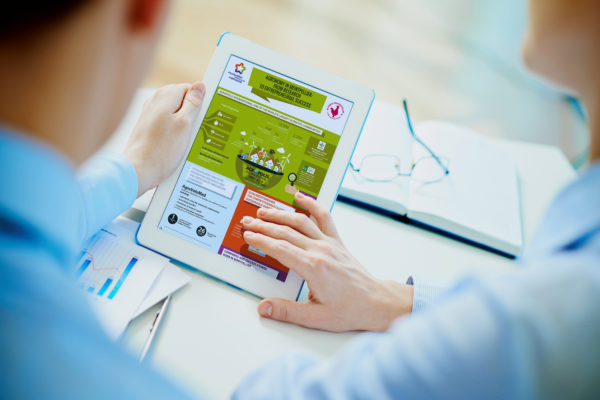 Close-up of business partners looking at business document in touchpad